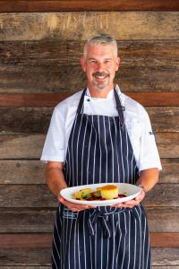 The Boat Shed Chef Holding Dinner Plate
